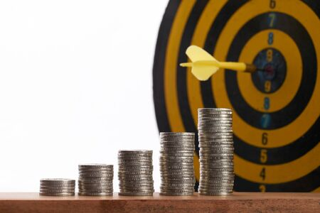 Yellow dart hit in the center of a target with stack of coins on white background with copy space. A idea about money  currency investment that must decide or think carefully Stock Photo