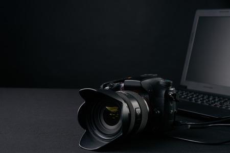Closeup of professional  photography camera,modern laptop, home illustration & equipments on creative desk . business conceptual Foto de archivo
