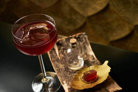 non alcoholic: Fresh branded red alcoholic cocktail with a small bottle for alcohol and a red marmalade snack on a black stone bar counter.  Concept of alcoholic and non-alcoholic bar beverage.