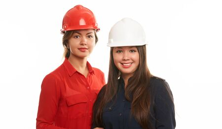 Portrait of two female engineers, construction workers in protective hard hat or helmet isolated on white. Safety concept