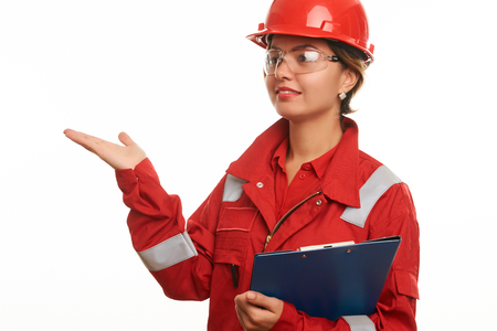 Engineer construction worker woman in safety uniform and red hardhat showing empty space on her palm and advertising. Isolated on white. Close-up portrait