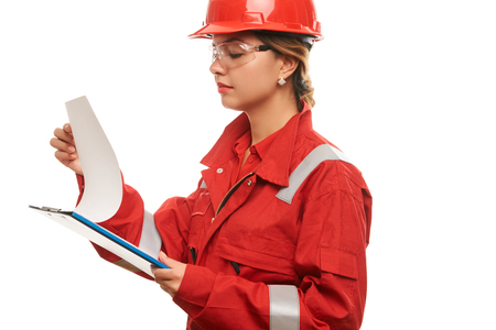Woman construction worker wearing hard hat and protective uniform with safety glasses, holding clipboard with blueprints isolated on white background. Close-up portrait