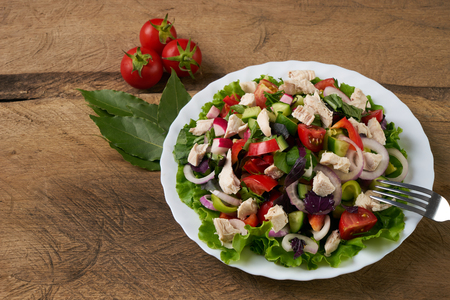 Fresh salad with fresh vegetables and chicken meat on old rustic wooden table, healthy food concept Stock Photo
