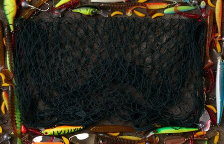 Frame of fishing tackle - fishnet, fishing rod, fishing line, hooks and baits on a wooden background. Top view, copy space.