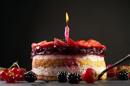 Fresh birthday fruit tart with strawberry blackberry currant and holyday candle isolated on black background with copy space Stock Photo