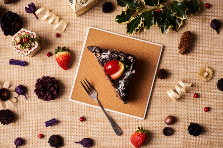 Slice of Christmas chocolate cake with strawberries, cherry, cream, biscuit on a dark slate cake board, and christmas decorations, fir cones, holly tree branch, gift boxes and berries, top view