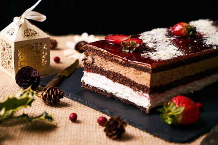 Delicious Christmas cake souffle with strawberries, caramel icing and white chocolate crumbs on black slate board with christmas decorations, fir cones, holly tree branch, gift boxes and berries Stock Photo
