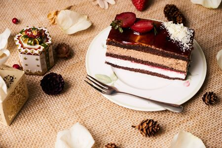 Slice of Christmas cake souffle with strawberries, caramel icing and white chocolate crumbs on white plate with christmas decorations, fir cones, holly tree branch, gift boxes and berries Stock Photo