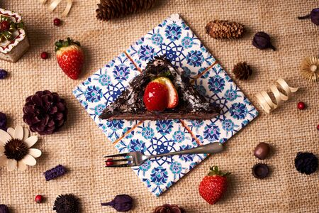 Piece of Christmas chocolate cake with strawberries, cherry, cream, biscuit on a dark slate cake board, and christmas decorations, fir cones, holly tree branch, gift boxes and berries, top view