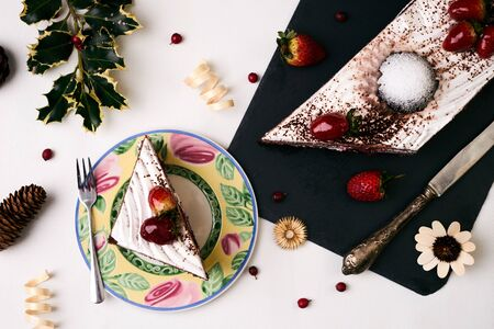 Christmas dessert. Cake with fresh strawberries . Slice of cake with souffle, strawberrie cream and chocolate crumbs with christmas decorations, fir cones, holly tree and berry on white background , top view