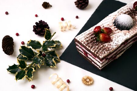 Homemade strawberry Christmas cake with fresh strawberries, souffle, cream and chocolate crumbs with christmas decorations, fir cones, holly tree and berry on blue background , top view