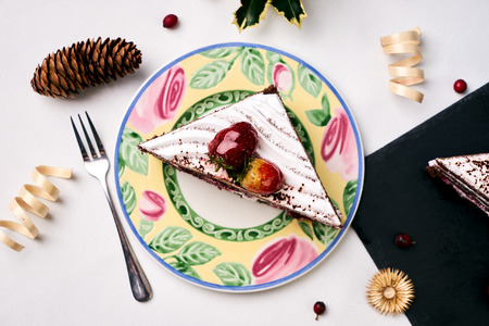 Traditional Christmas fruit cake with fresh strawberries, souffle, cream and chocolate crumbs with christmas decorations, fir cones, holly tree and berry on blue background, new year holiday dessert