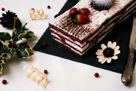 Christmas dessert. Fresh strawberry cake souffle cream and chocolate crumbs with christmas decorations, fir cones, holly tree and berry on black slate cake board on white table. Festive new year food Stock Photo