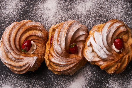 Profiterole, french puff pastry eclairs with custard cream, strawberry and powdered sugar on dark slate cake board on blue background, close-up, top view. Stock Photo