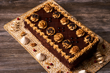 Chocolate cake with walnut and  whipped custard sour cream on cake board with decorations, close-up. Sweet dessert food Stock Photo