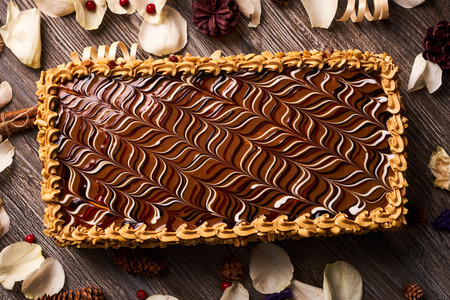 Peanut cake with chocolate and whipped custard cream on wooden table background with christmas decorations, sweet dessert food