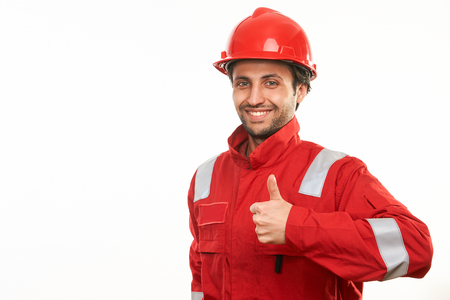 Smiling and successful construction worker in helmet and uniform posing showing thumbs up gesture, isolated on white background with copy space, close-up portrait Stock Photo