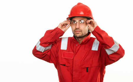 Young construction worker builder in red hard hat and workwear uniform thinking about something, isolated on white background with copy space, close-up portrait.