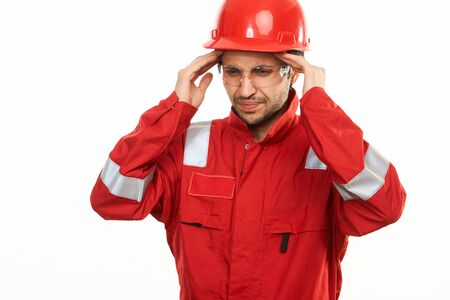 Young engineer worker in red helmet suffering stress working isolated on white background. Close-up portrait