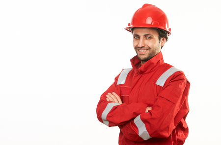 Professional engineer worker in a helmet and red protective workwear uniform holding his hands crossed isolated on white background with copy space. Close-up portrait