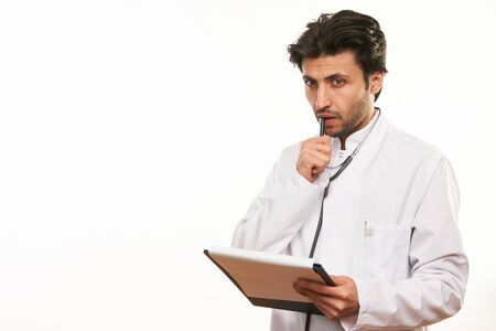 Young male doctor holding clipboard and looking at it while standing against white background with copy space, Thinking about proper medication