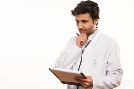 Young doctor writing notes on clipboard paper as copy space for patients medical history. Healthcare and medicine concept Stock Photo