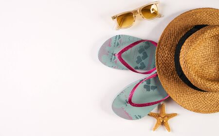 Summer beach womens accessories straw hat, sun glasses, shoes and sea star isolated on white background with copy space. Summer holiday background. Top view