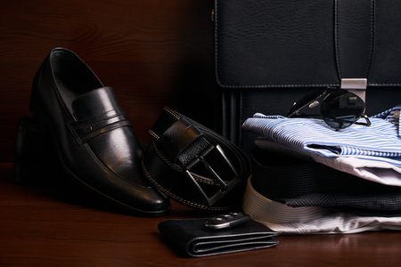 Set of mans fashion clothing and business accessories, black leather suitcase, shoes, belt, purse, glasses, shirts and car keys on wooden background. Mens fashion, close-up Stockfoto