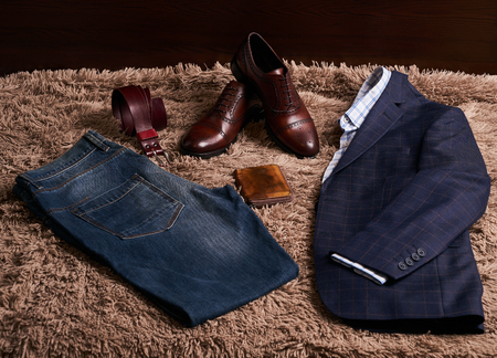 Set of classic men's clothes such as dark suit jacket with light shirt, jeans trousers, brown leather shoes, belt and wallet on soft carpet background.
