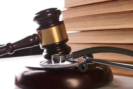 Judge's Gavel and medical stethoscope with books on table, close-up. Medicine law concept