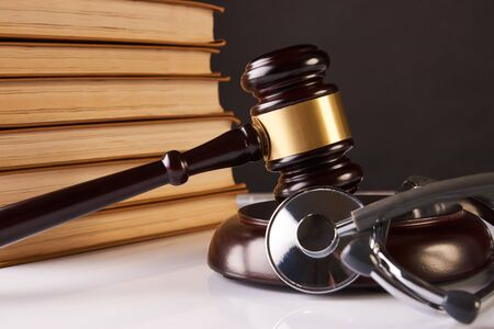 Judges Gavel and medical stethoscope with books on table, close-up. Medicine law concept