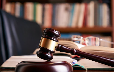 Judge gavel or law mallet and eyeglasses on a wooden desk, law books background. Education and legal law concept 스톡 콘텐츠