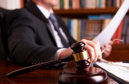 Lawyer working, holding Law document with judges gavel at desk in courtroom lawyer office, tribunal and justice concept