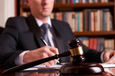 Judge or lawyer working with agreement in courtroom theme. Justice and Law concept with judge's gavel on wooden table with law books on background Banque d'images
