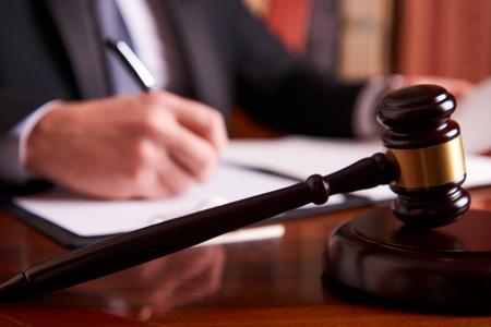 Młotek sędziego na drewnianym stole i adwokat pracujący na sali sądowej. Pojęcie prawa sądowego