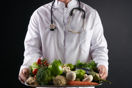 Doctor nutritionist holding a tray of fresh organic vegetables. Health care and medical concept. Healthy eating and Detoxification concept. 版權商用圖片