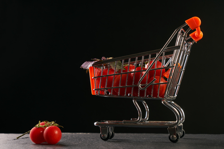 Fresh vegetables in shopping cart. Grocery shopping cart with vegetables fresh juicy tomato isolated on black background with copy space.