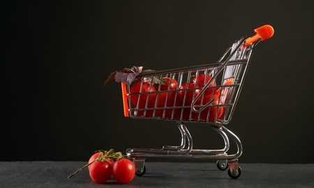 Grocery shopping cart with fresh vegetables. Fresh raw tomato and basil in shopping cart in market isolated on black background with copy space. Stock Photo
