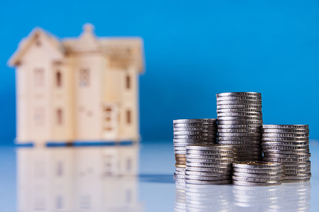 A stacking coins and house model on blue background with copy space.