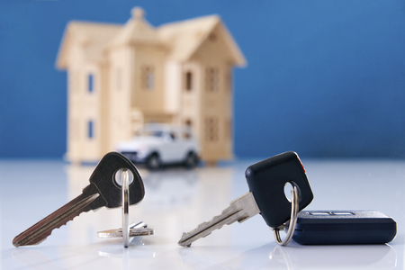 Car key and house keys with new automobile and home
