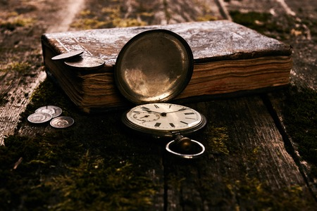 Pocket watch with an old antique bible book and ancient copper c