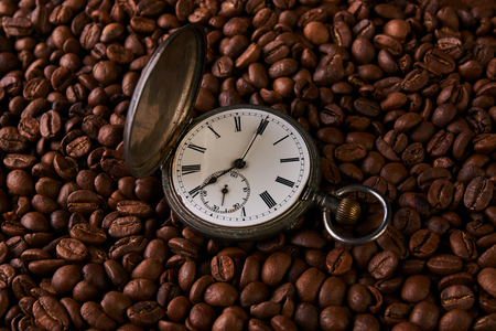 Old vintage pocket watch in roasted coffee beans