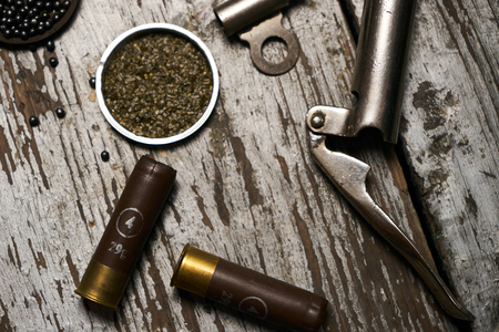 Shotgun, hunting cartridges with gunpowder and many plumbeous fractions, lead shot on wooden table background. Hunting equipment