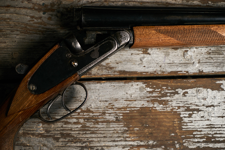 Hunting shotgun riffle on old rustic wooden table Stock Photo