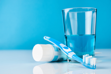 A blue toothbrush with toothpaste and glass of blue mouthwash on blue background with copy space, close-up. Dental oral hygiene concept