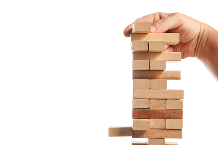 Wood block tower game on white background. Planning, risk and strategy of project management in business, businessman and engineer gambling placing wooden block on a tower. Construction concept.