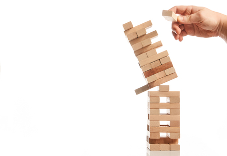 Businessman hand take one block from tower of wooden blocks and tower collapses on white background with copy space. Strategy game as a business plan for team work Foto de archivo