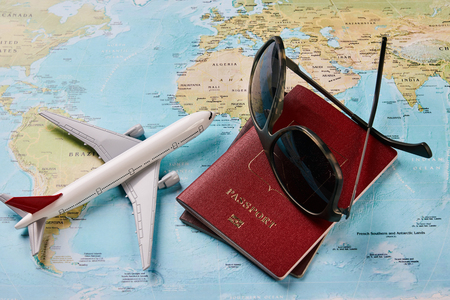Airplane with two passports travel documents and sunglasses on the map of the world, holidays abroad. Plane worldwide travel planning concept. Traveling vacation concept, close-up Stock Photo