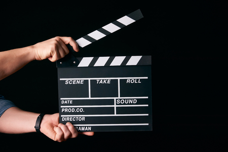 Hands with a movie clapperboard isolated on black background with copy space, close-up. Wooden clapper board as cinema and movie time concept Stok Fotoğraf