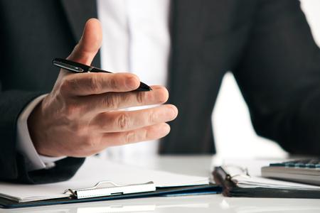 Geschäftsmann, der am Tisch sitzt und etwas, Nahaufnahme erklärt. Verkaufsangestellterversicherung, die versuchend spricht, zum Kunden am Schreibtisch im Büro über weißem Hintergrund zu überzeugen